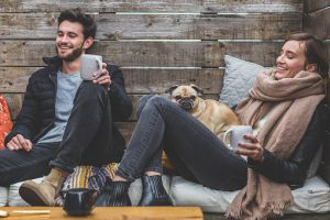 A young man with a coffee and a young woman with coffee and a dog on her lap sit on the floor both with big smiles