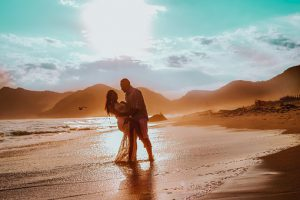 sun shining the ocean in foreground mountains in the background while A couple embrace