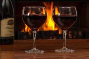 Two reds wines sit on a table ready to go in front of a nice warm open fire