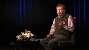 Eckhart Tolle sits in a chair speaking wise words of wisdom to his audience