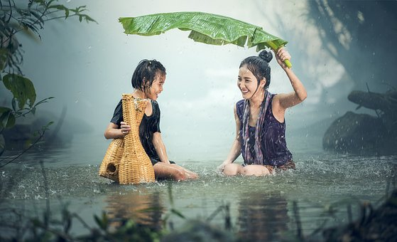 two girls shelter from rain under a banana tree leaf
