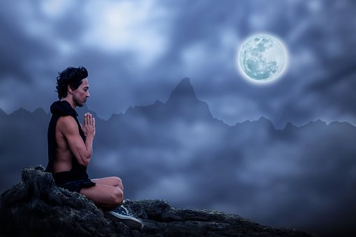 man meditates high in the mountains at night with a perfect full moon